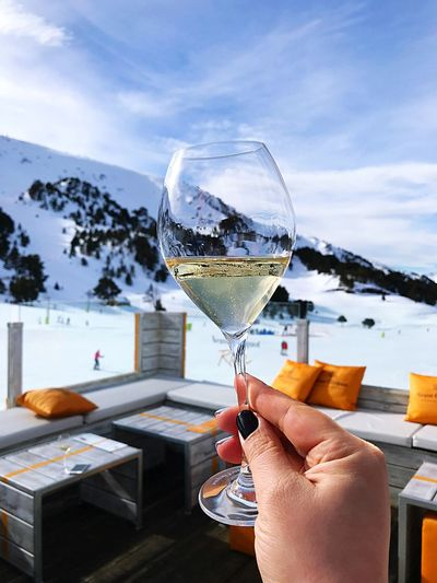 Woman Holding Champagne Flute Against Snowcapped Mountain
