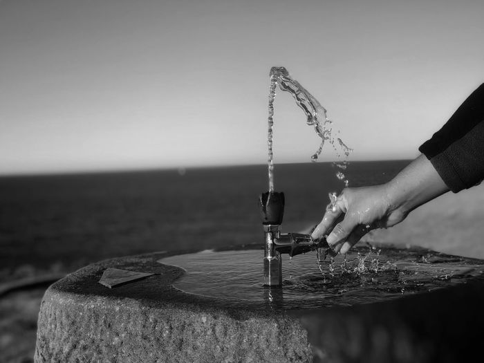 Cropped hand at drinking fountain by sea against clear sky