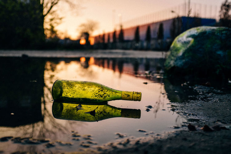 Reflection of bottle on puddle at road