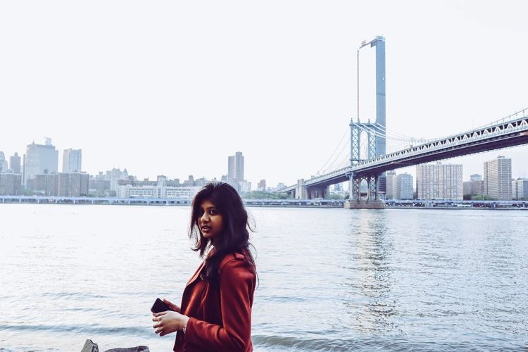 Portrait of young woman standing by east river in city