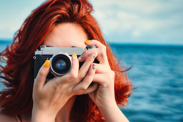 Red haired woman travel photographer, taking pictures on the background of the sea.