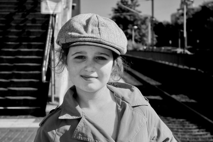 Close-up portrait of girl standing at railroad station