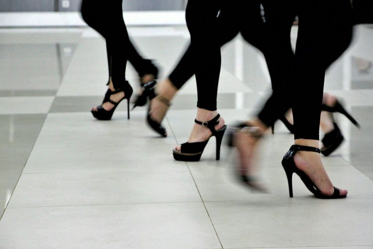 Low section view of women wearing high heel sandal