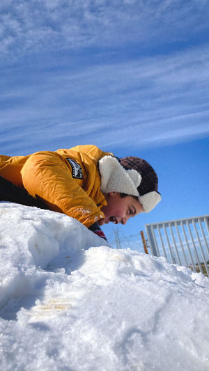 Rear view of child in snow against sky