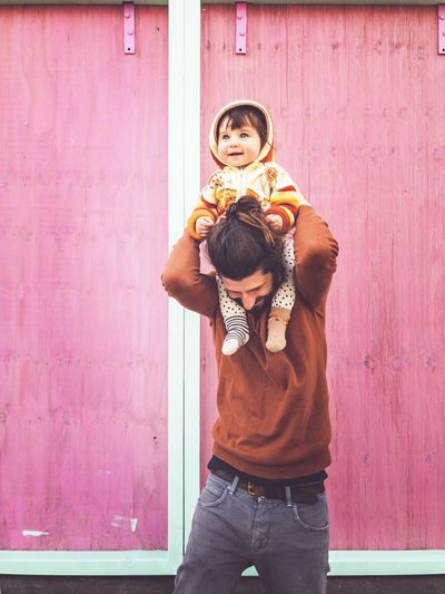 father carries his baby on his shoulders Fashion Babyhood Baby Young Urban Happiness Happy Baby Cheerful Fatherhood Moments Father Daddy Father And Daughter Family Carry Carrying Carrying On Shoulders Pink Background Pink Toddler  Fun Childhood Standing Child Wall - Building Feature Three Quarter Length Lifestyles Casual Clothing Real People Offspring Emotion