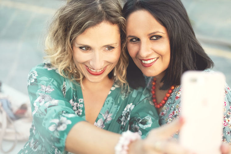Middle aged beautiful women taking a selfie outdoor with a smartphone in the summertime. Smiling Portrait Happiness Two People Emotion Togetherness Women Young Adult Young Women Adult Headshot Looking At Camera Bonding Friendship Casual Clothing Hairstyle Positive Emotion Front View People Beautiful Woman Smart Phone Selfie Self Portrait Adult Mid Age Aged Mid-air Beautyful  Summer Vivid Color Dressing Up Outdoors Fun Having Fun Relaxing Park Seaside Harbor View Top Brunette Blonde Cell Phone Photography Technology Instagram Social Media Taking Photos Making Pictures