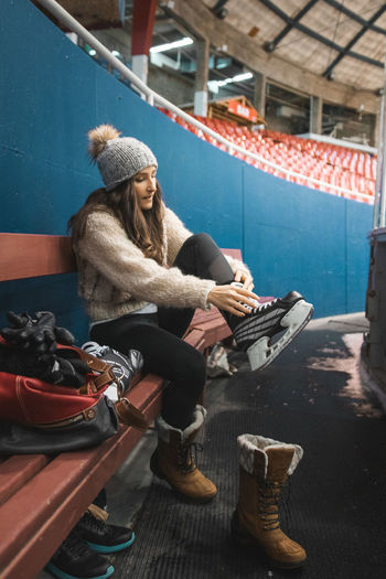 Full length of woman wearing skate while sitting on bench