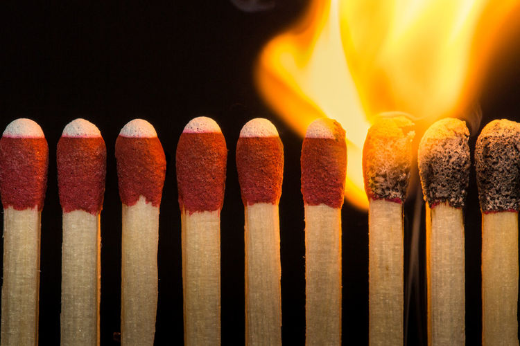 Close-up of burning matchsticks against black background
