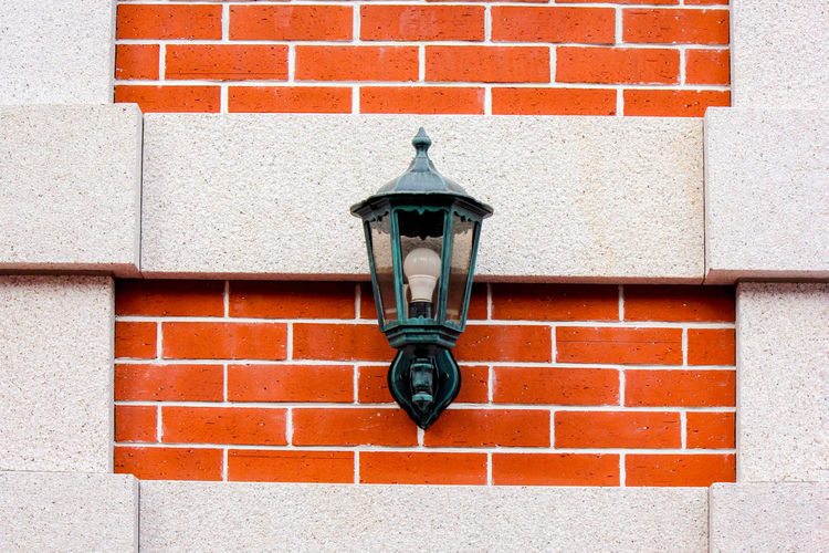 Close-up of street light against brick wall
