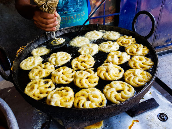 Jalebi an indian sweet dish being fried in sugar syrup in a large container Jalebi Business Close-up Day Food Food And Drink Freshness Fried Sweets Frying Pan Healthy Eating High Angle View Holding Household Equipment Human Body Part Human Hand Indoors  Jilipi Kitchen Utensil One Person Preparation  Preparing Food Real People Sugar Syrup Sweet Dish  Wellbeing