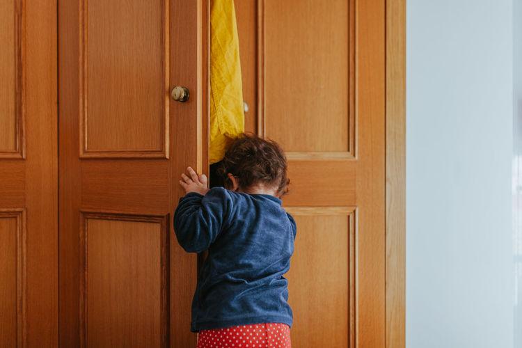 Rear view of baby girl looking through door