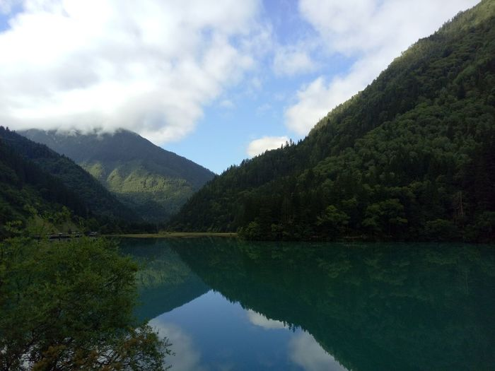 Scenic view of lake and mountains against cloudy sky at jiuzhaigou