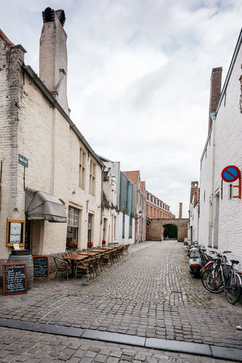 Empty street in Bruges a cloudy day of summer Architecture Belgium Bruges Brugge Building Exterior Built Structure City City City Life Cityscapes Cloud - Sky Day Empty No People Outdoors Perspective Road Sky Street Tranquility Travel Destinations Urban