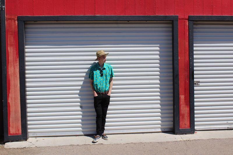 Full length of man standing against shutter