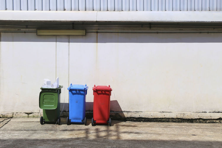Three color plastic recycle bin Day Nature Outdoors Built Structure Architecture Building Exterior Footpath Sunlight Garbage Bin Recycling Bin Recycling Garbage Can Container Plastic No People Wall - Building Feature Environmental Conservation Industry Environment Red Blue Green Color Plastic Bag City Hygiene