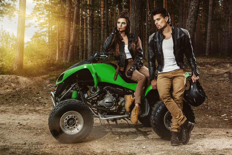 Full length of man and woman wearing leather jacket by quadbike in forest