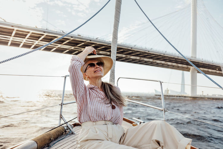 Senior woman sitting on boat against sea