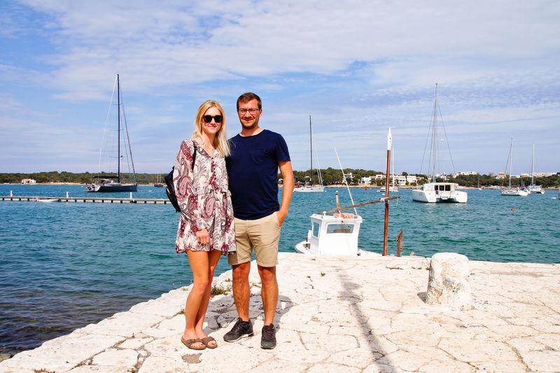 Full length portrait of couple standing on harbor against sky