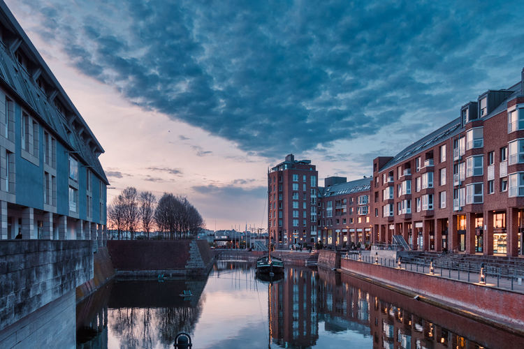 Canal amidst buildings in city against sky at sunset