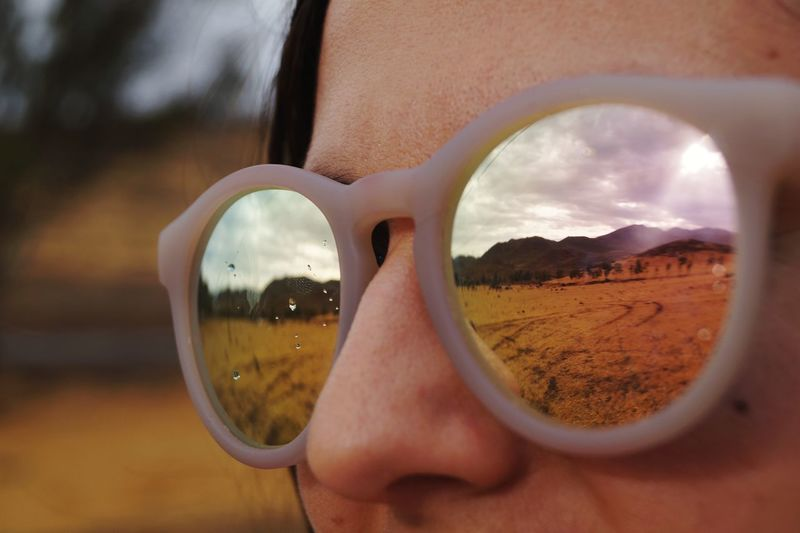 Cropped image of woman wearing sunglasses with reflection