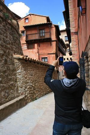 One men is taking photo with mobile phone in old Spanish town Albarracín. Albarracín Taking Photos Architecture Building Exterior Built Structure Casual Clothing Leisure Activity Lifestyles Men Mobile Photography One Person Photographing Photography Themes Rear View Technology Unrecognizable Person