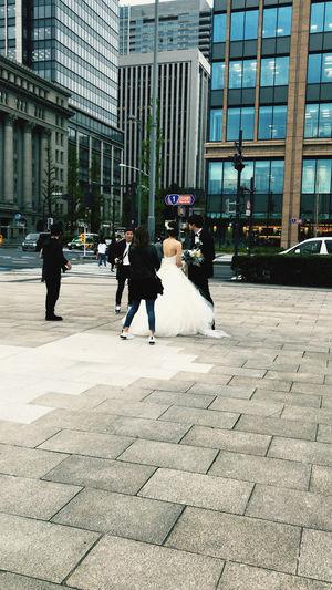 People walking on footpath amidst buildings in city