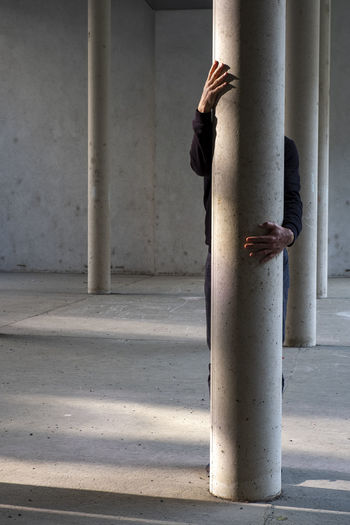 Men standing by column