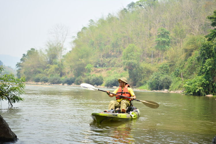 Water Outdoors Chiang Rai, Thailand Nautical Vessel Oar Transportation Tree River Plant Day Nature Kayak Leisure Activity Adult Men People Adventure Sitting Rowing Paddling