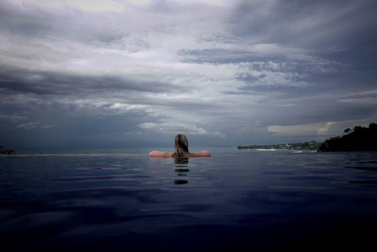 Rear view of woman swimming in pool