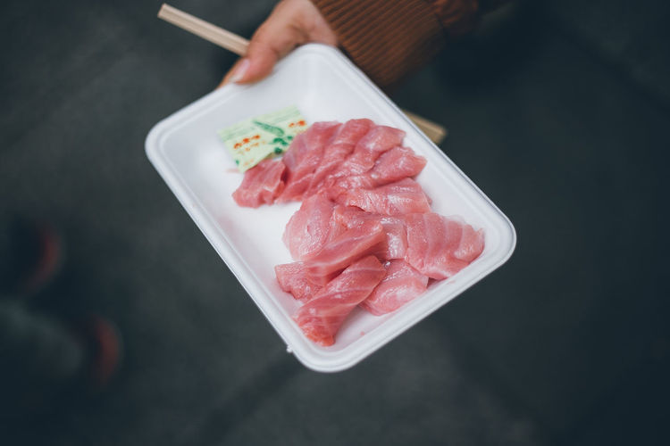 Close-Up High Angle View Of Hand Holding Sashimi