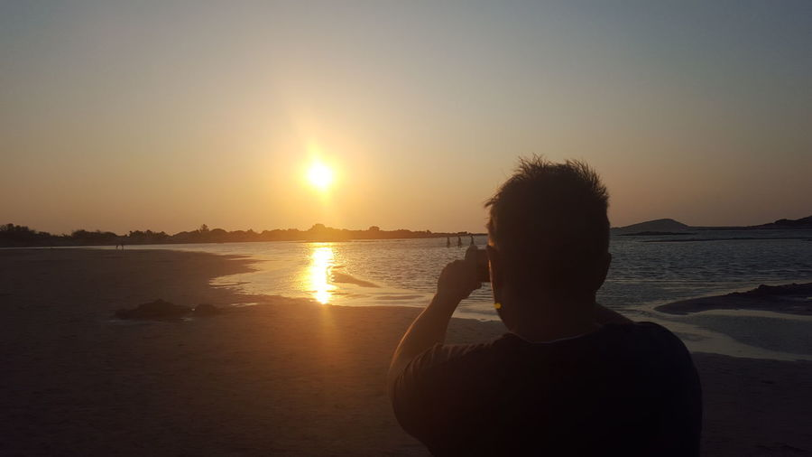 Rear view of silhouette man photographing at beach during sunset