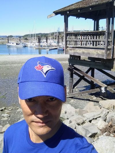 Self portrait at beach, Salt spring island, Canada Salt Spring Island Mobilephotography Sea Low Tide Seaside Cap Asian  Asian Man Travel Traveling Blue Pavillion Wooden Mobile Photography Stine Boay Summer British Columbia, Canada Man Menswear Water Nautical Vessel Sea Beach Sand Headshot Portrait Architecture Sky