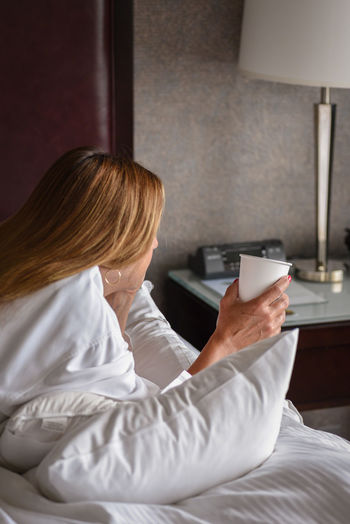 Woman Holding Coffee Cup While Lying On Bed At Hotel