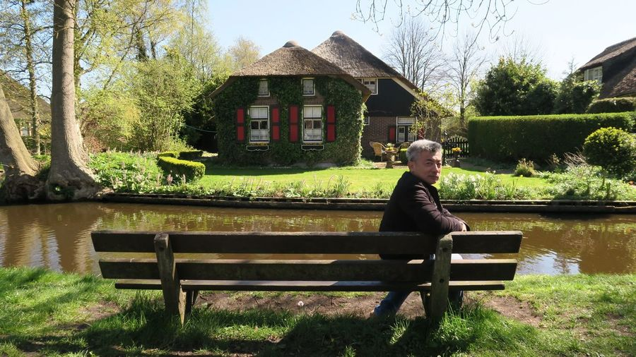 Portrait Of Man Sitting By Canal On Bench