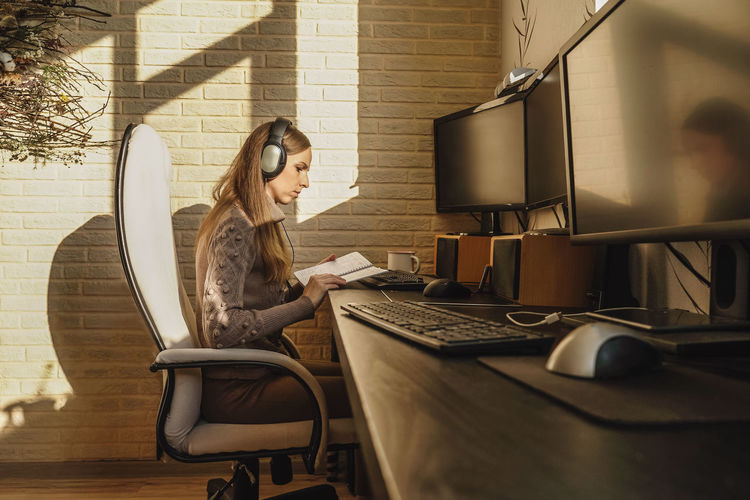 Woman reading book by computer on table