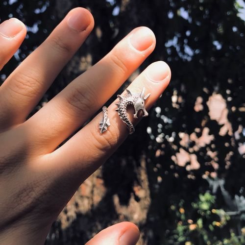 Cropped hand of woman wearing ring against trees