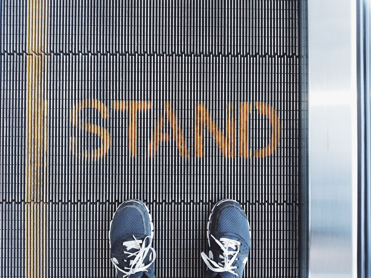 Low section of man standing on escalator with text