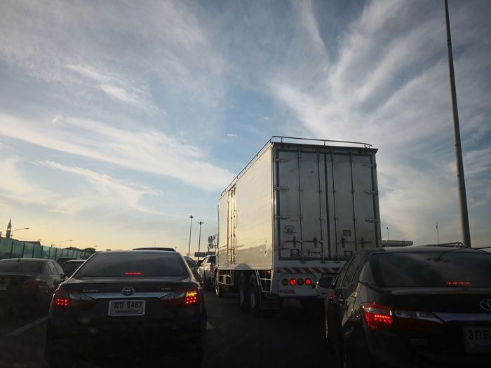 Traffic on road in city against sky