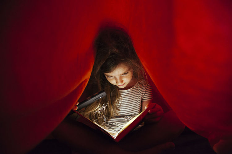 Close-up of girl with mobile phone light reading book under blanket