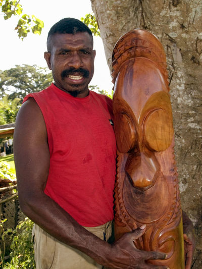 Melanesian Wood Carver, TamTam Slit Drum, Vanuatu. 2007 .In Vanuatu, a slit drum is a musical instrument that is traditionally played by men of high rank. On the island of Ambrym though, such drums stand vertically on the ground; they are decorated with one or several faces with disk eyes, representing ancestral figures, such a figure is called a tamtam.The distinctive shape of these Ambrym drums has made them iconic of Vanuatu as a whole; they are frequently found in museums around the world, represented on Vanuatu banknotes. The drums are sometimes found at ceremonial dance grounds and other gathering places. They have been used for dance rhythms, but also for signalling purposes. A tamtam is said to hold spirits, some good, some bad, and are often posted upright at the perimeter of a property or outside a house as protection. Melanesian Slit Drum Tam Tam Wood - Material Woodworker Carpentry Carving - Craft Product Carving Hard Wood Melanesia New Hebrides Craftsmanship  Production Art And Craft Travel Destinations Tourism Tamtam Ceremonial Pacific Ocean
