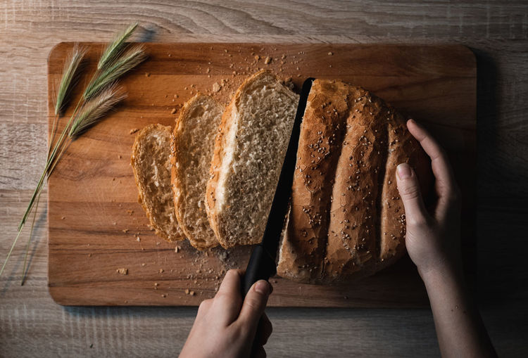 Directly above shot of person holding bread on cutting board