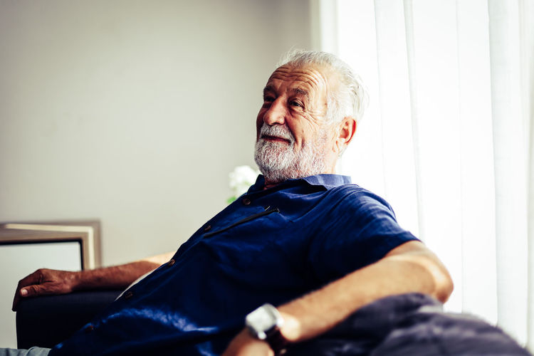 Man looking away while sitting at home