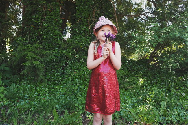 Grass One Person One Girl Only Childhood Girls Children Only Child Standing Portrait Outdoors Green Color Tree Looking At Camera People Front View Day Summer Blond Hair Real People Nature Bonnet Tiny Bouquet Flower The Portraitist - 2017 EyeEm Awards