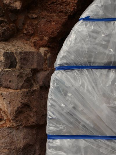 Polythene wrapped by stone wall