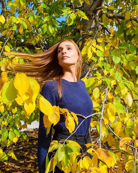 Beautiful young woman standing against yellow plants