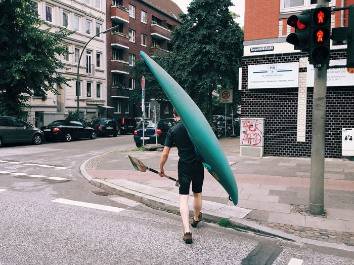 Rear View Of Man Carrying Canoe And Oar On Street In City