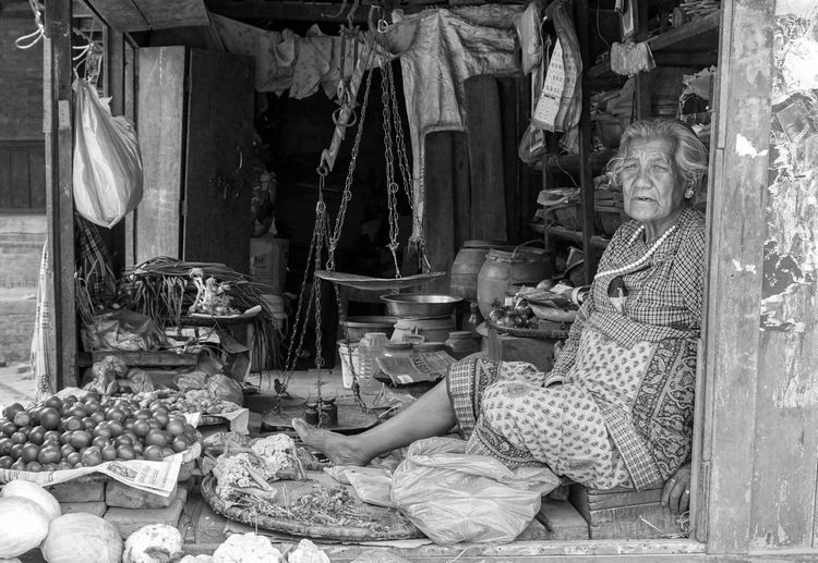 Portrait Of Senior Woman Selling Vegetables At Market Stall