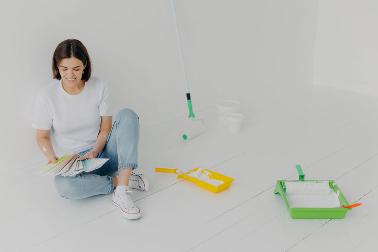 Full length of woman holding color swatch sitting on floor at home