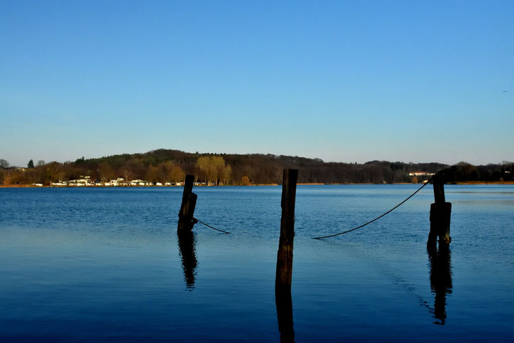 Man on wooden post in lake against clear blue sky