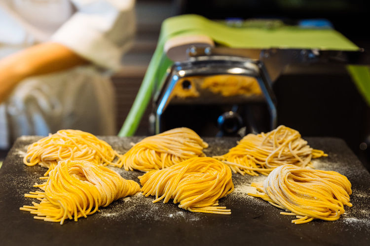 Homemade piles of fresh egg spaghetti pasta that powdering flour to keep them from sticking. Pasta Food Food And Drink Italian Food Freshness Focus On Foreground Indoors  Preparation  Table Raw Food Yellow Healthy Eating Wellbeing Selective Focus Close-up Tagliatelle People Incidental People Still Life Spaghetti